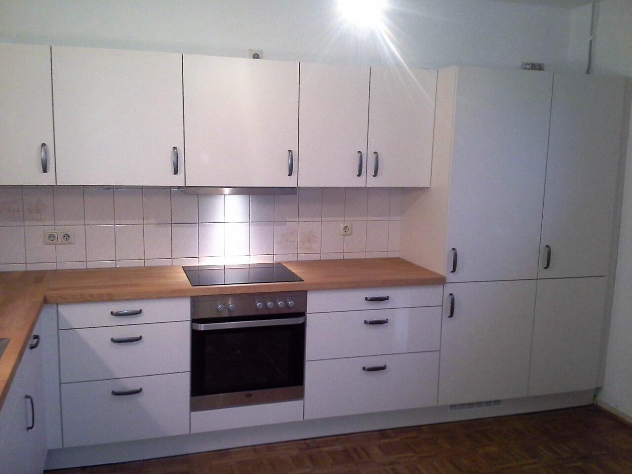 eine große Küche, schlicht Weiß mit Echtholzarbeitsplatte